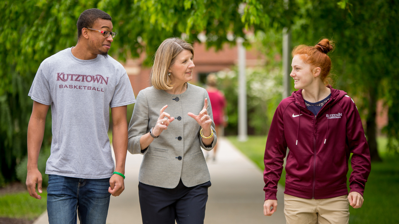 Prof. Elizabeth Rogol walks and talks with two students on campus.