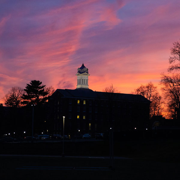 image of the darkened outline of old main clock tower against a pink and blue sky at sunset