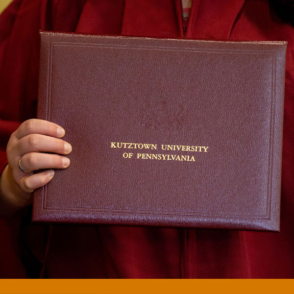 image of a hand holding a ku embossed diploma against the traditional maroon robe worn by graduates