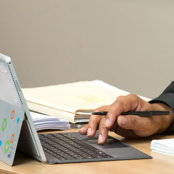 Photo of a laptop computer with an african american hand holding a pen and also typing on the keyboard with a stack of files in the background