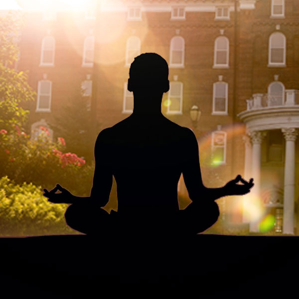 Outline of a yoga meditation pose in front a a sun soaked outdoor image of the front of the old main building