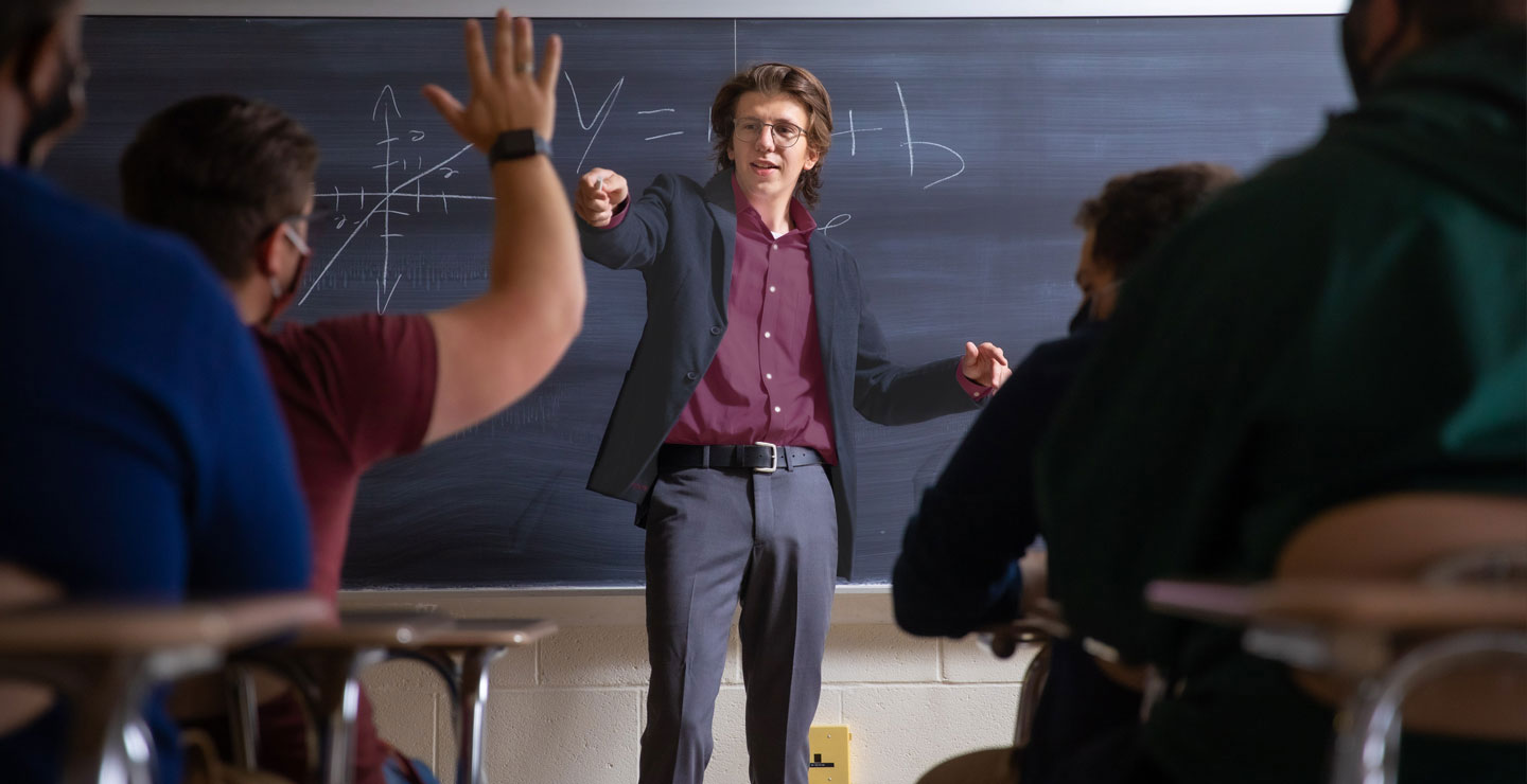 Male teacher in classroom pointing at student with hand raised.