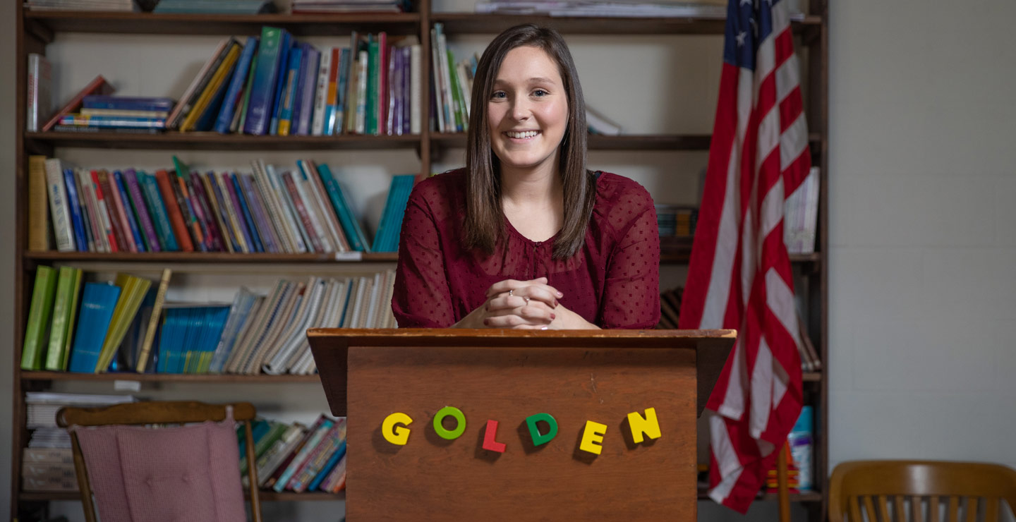 "Caucasian female student standing with her hands folded at a podium reading ""Golden"". A bookshelf, flag, and chair are behind her."