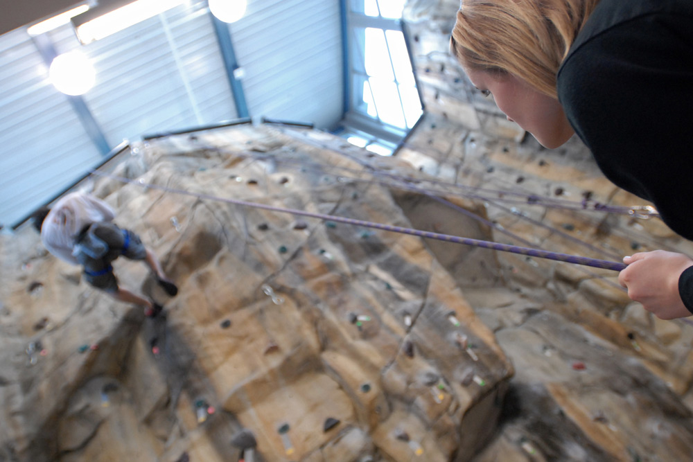 view from below as climber scales rock wall